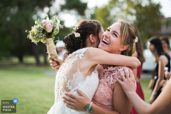 Nouvelle-Aquitainewedding photography for Seyches, France - bride and bridesmaid hug after toss of bouquet