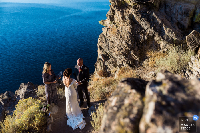A couple elopes at the top of Cave Rock overlooking Lake Tahoe in Glenbrook, NV