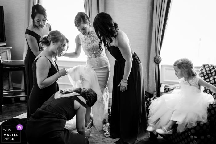 Hotelfotografie am Hochzeitstag - Brautjungfern helfen der Braut, ihre Schuhe anzuziehen, während das Blumenmädchen zuschaut