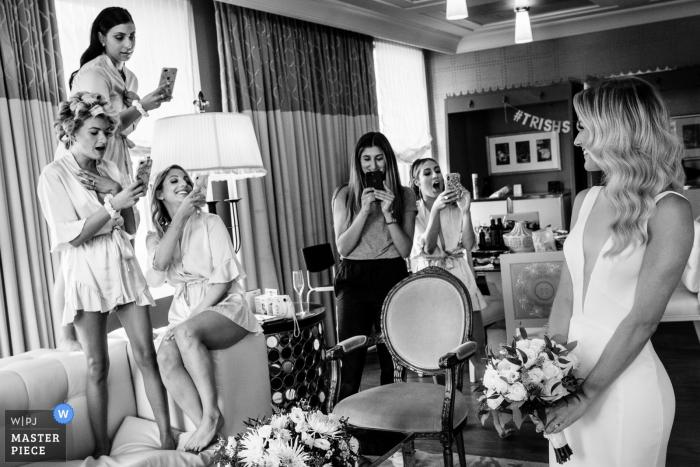 Hotel Getting Ready-Fotos - Brautjungfern und Friseur, die die Braut auffordern, sich zu posieren, bevor sie in ihre Zimmer aufbrechen, um sich anzuziehen.