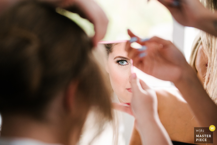 Ontario bride's house wedding day photography — bride peeks in the mirror at her makeup while the hairstylist works on her hair