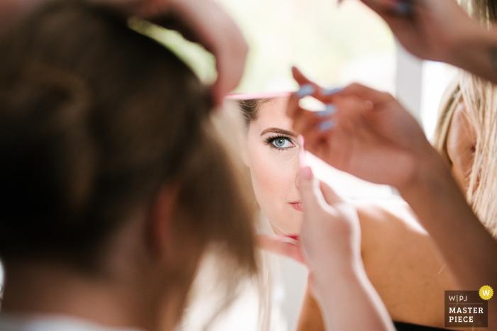 Hochzeitstagphotographie des Ontario-Brauthauses - Braut späht in den Spiegel an ihrem Make-up, während der Herrenfriseur an ihrem Haar arbeitet