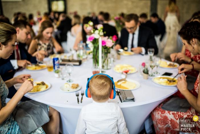 Brickhouse Hochzeit Veranstaltungsort Fotograf - Kind mit den Kopfhörern während der Mahlzeit an der Rezeption