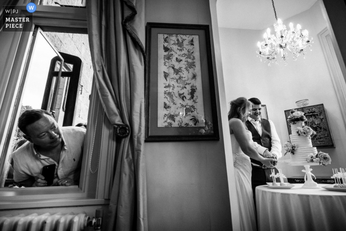 Wadhurst Castle, UK Wedding Venue: photo of a mirror reflecting the bride and groom cutting the cake, while a  man peeks through a window.