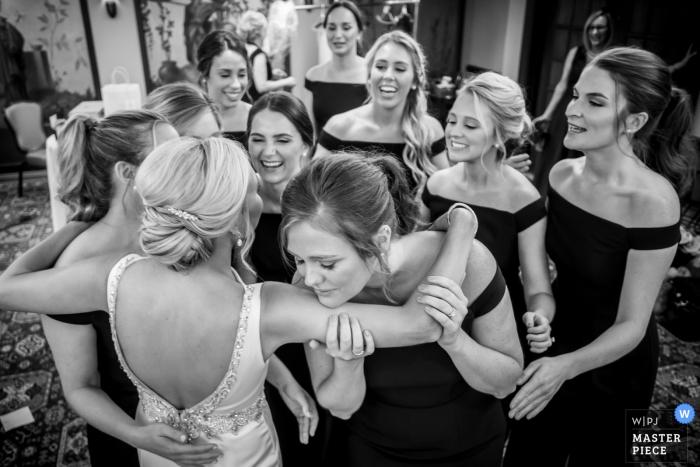 Brautjungfern sehen die Braut zum ersten Mal in ihrem Hochzeitskleid auf diesem Schwarzweißfoto im Detroit Athletic Club in Michigan.
