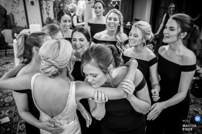 Bridesmaids see the bride in her wedding dress for the first time in this black and white photo at the Detroit Athletic Club in Michigan.