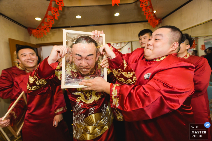 Fujian wedding image of the groom games - pushing his head through a frame wrapped in cellophane.