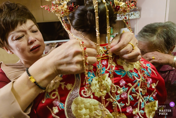 Fujian wedding photograph of the bride's mother helping the bride get ready while in tears prior to the wedding ceremony.