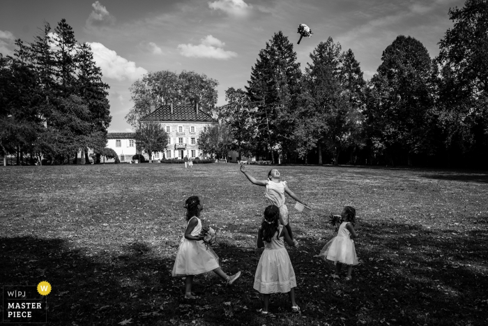 France wedding image of four little girls throwing the bouquet into the air during play at the reception.