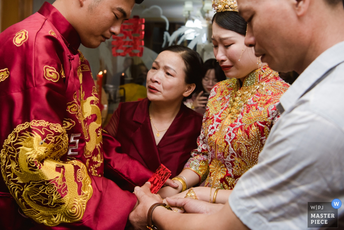 China wedding photo of the bride and groom holding hands with mother and father for an emotional moment.