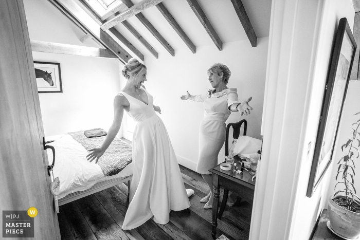 The bride & her mother open arms, ready to embrace. Preparations are complete, everything perfect & ready to head to the church for the wedding ceremony. in Hampshire, UK.