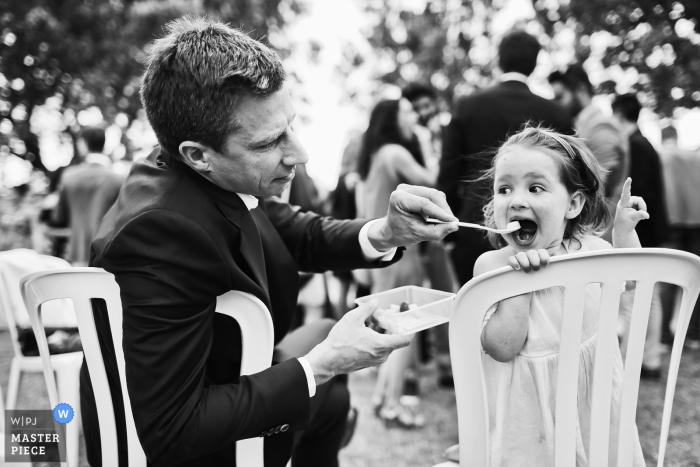 During the cocktail session at a wedding a dad is feeding her daughter at the Domaine de Sarson in Grignan, France