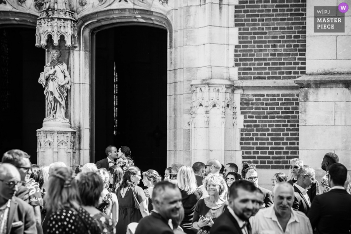 France wedding photography at the Church — Stolen kiss outside with the guests