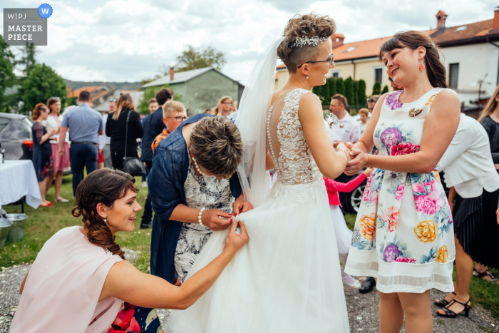 Knezak Wedding Photographer — Fixing the wedding dress during congratulations after the church ceremony.