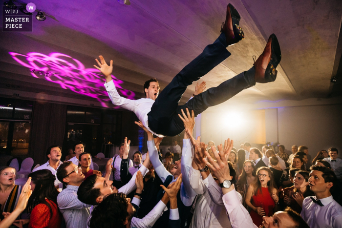 Flanders wedding reception venue photography | Groom is tossed up in the air during the party