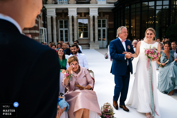 Flanders Outdoor Wedding Ceremony Photographer — Father of the bride is about the give away his daughter while her mom sheds a tear of joy, the bride looks full of excitement to the groom