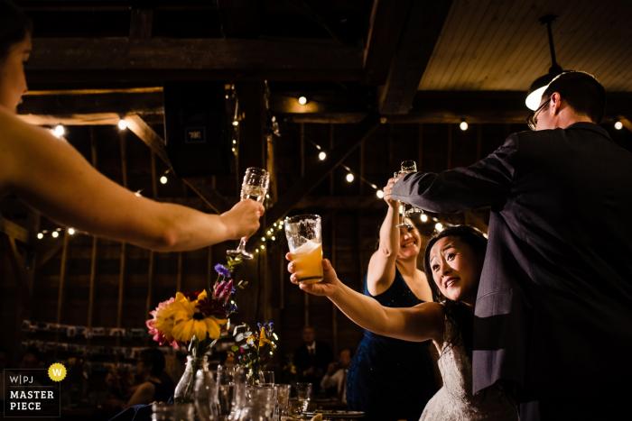 Wedding venue: Farmhouse Inn at Robinson Farm — wedding day photography | The bride and groom toast with their friends