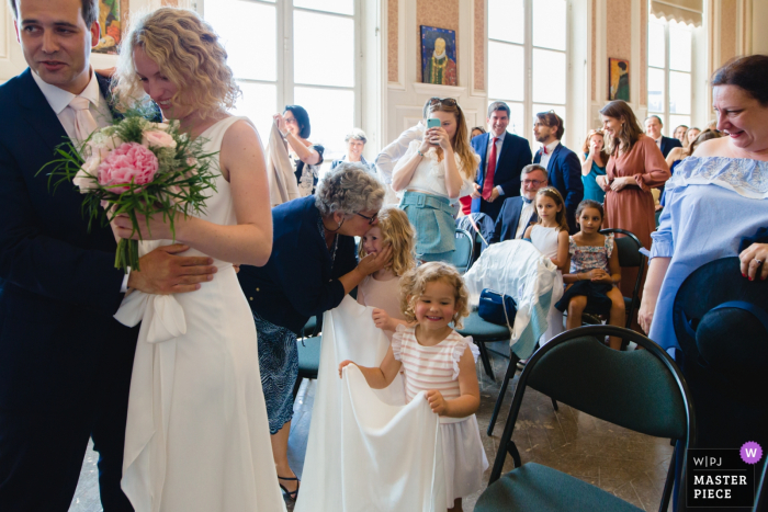 During ceremony, the flower girl gets a kiss behind the bride and groom — Paris wedding photographer