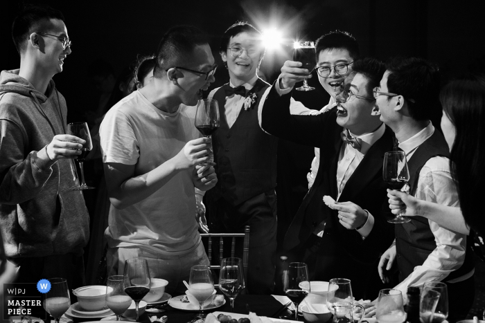 China Hotel wedding venue reception photography — The bridegroom laughed at a large glass of red wine prepared by his friends during the toast