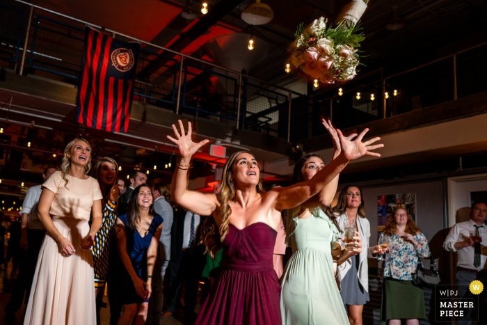 Wedding Venue Photography: Torpedo Factory, Old Town Alexandria VA — bridesmaid almost catches the bouquet