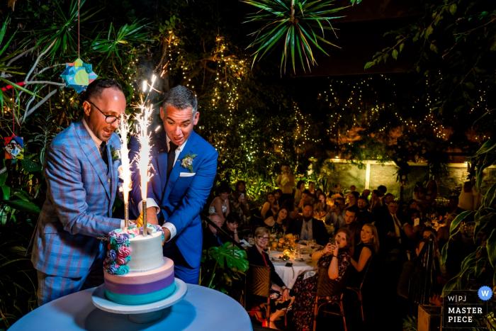 Michael's Restaurant, Santa Monica CA wedding venue photos — grooms cut into their firecracker topped unicorn wedding cake