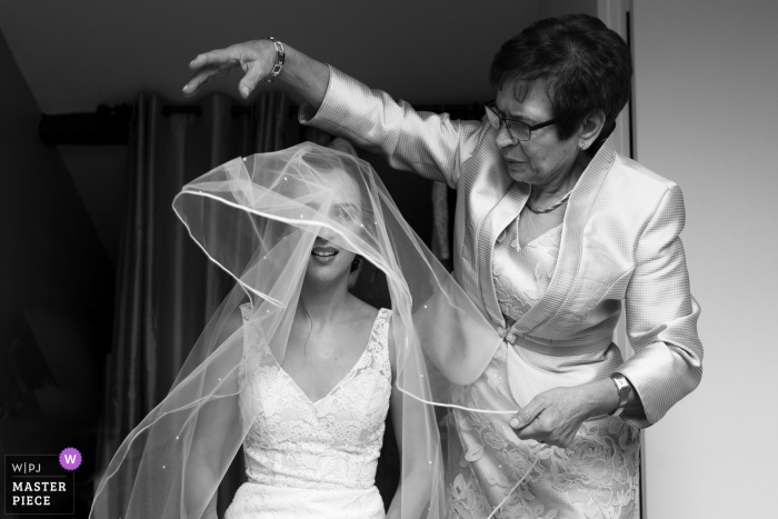 Paris wedding photographer: The mother of the bride is helping her with the veil