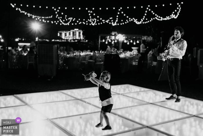 The Ritz Dubai Wedding Photos - Ein kleiner Junge, der zum Saxophon tanzt