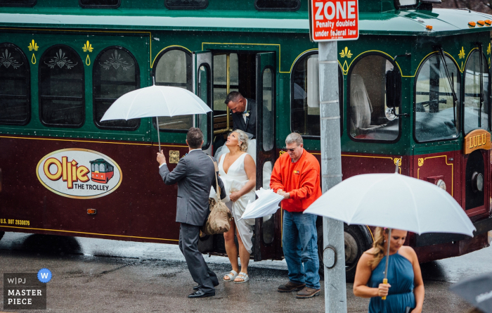 Nebraska	Ceremony Photography - The Bride getting off of trolley looking up at it raining - Ollie The Trolley