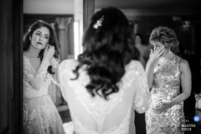 Empfangsort Fotografin für NJ - Bride, die den letzten Schliff gibt, als sie kurz vor der Zeremonie steht. Währenddessen schaut ihre Mutter zu und wird emotional.