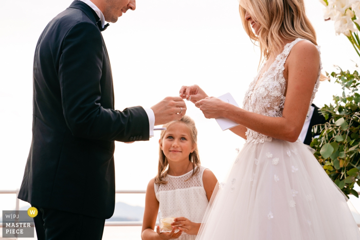 Belgium Wedding Ceremony Photos – A Girl looks admiringly when the bride is about to put on the ring
