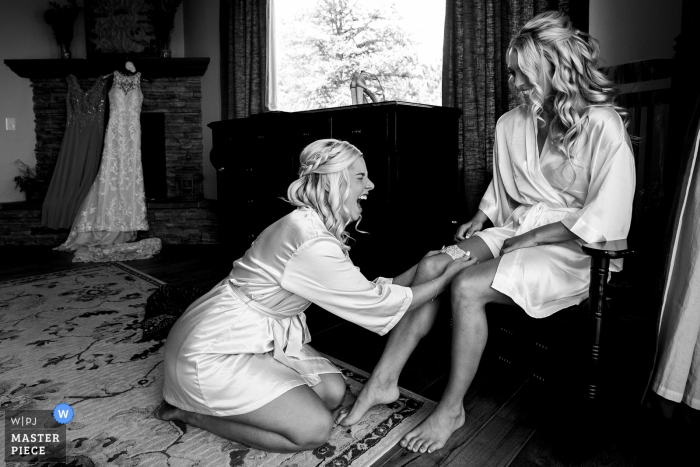 The Broadmoor - CO wedding photographer - The maid of honor laughs while placing the garter on the bride while getting ready for the wedding.