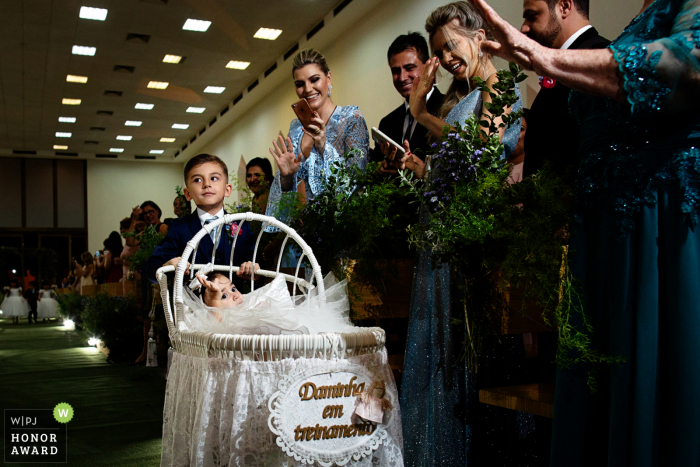 Brazil wedding ceremony photo of the ring bearer pushing baby down the aisle.