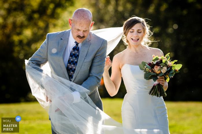 Hochzeitsfotograf für das Sugarbush Resort - Warren, VT - Der Stiefvater der Braut verheddert sich im Schleier, als er sie den Gang entlangführt.