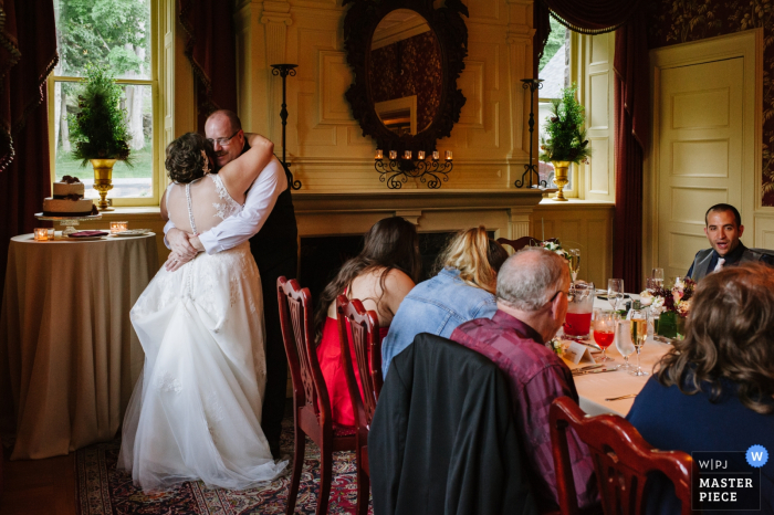 Wedding photography from the Inn at Erlowest, Lake George, NY | A bride and groom dance together closely during dinner at their wedding.