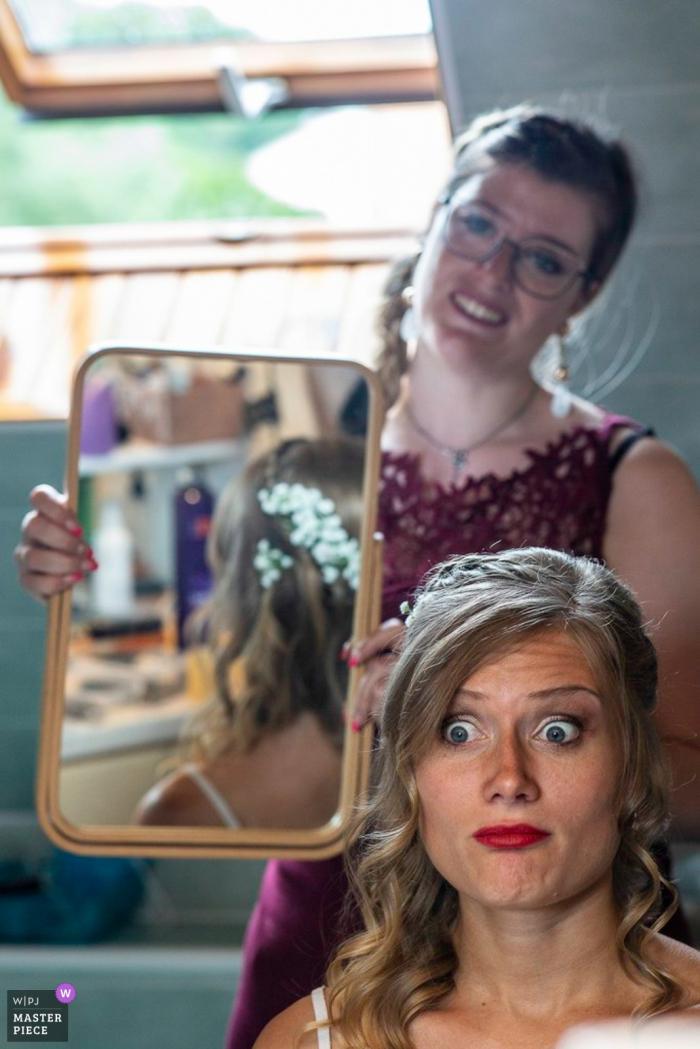 Lièpvre macht sich für die Hochzeitsfotografie fertig - Braut überprüft ihr Haar im vertikalen Spiegel.