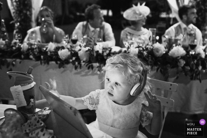Abbaye de Taloire France wedding photography - a little girl watch her tablet during the speeches
