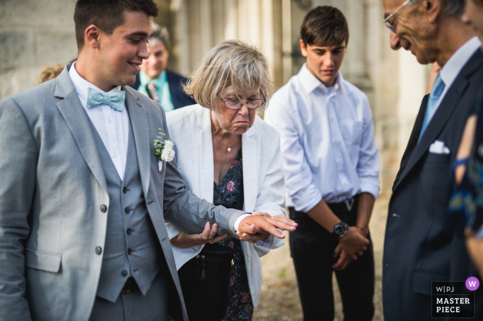 Agen, France wedding photograph of the groom showing off his ring to other guests after the ceremony