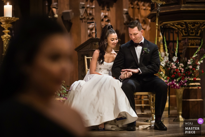 NJ Wedding Ceremony Photographer: Bride and Groom check out thier rings during communion