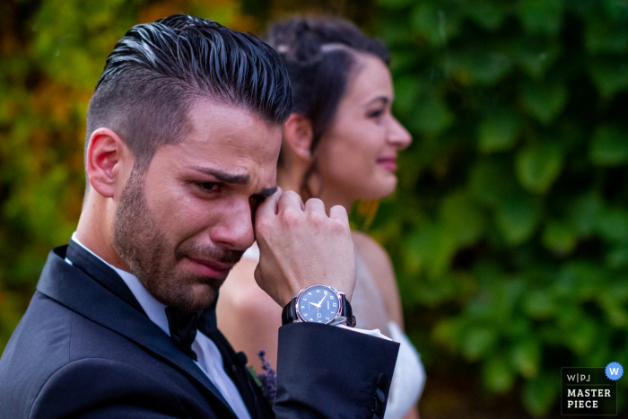 Lunario - Valverde wedding picture showing the bride wiping a tear with is bride behind him.
