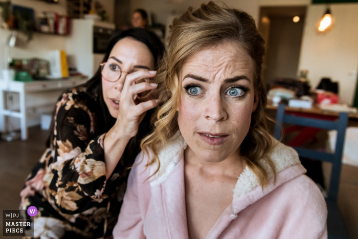 Holland - Rotterdam wedding reportage photographer: Bride looks in the mirror with her make-up artist