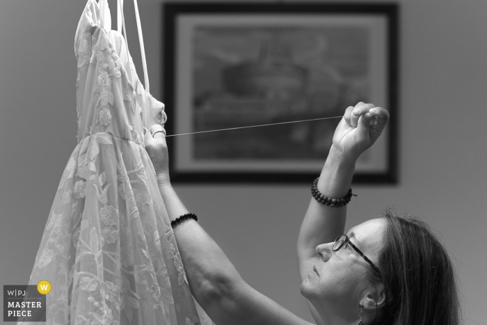 Tuscany bride's mom repairing the dress at last moment - Italy wedding photography