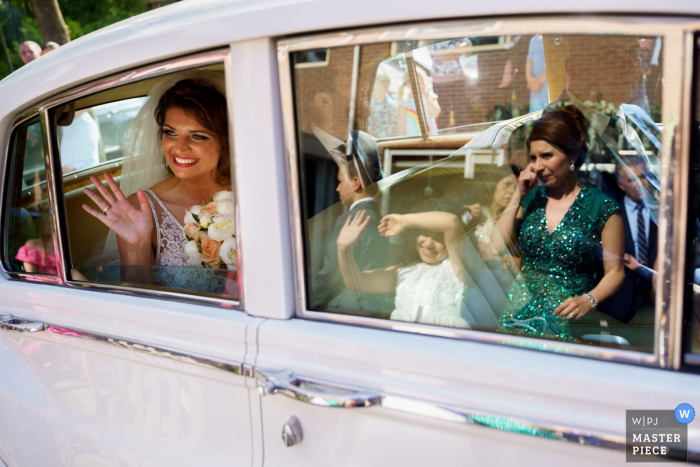 Enschede bride Waving from the car in this wedding image.