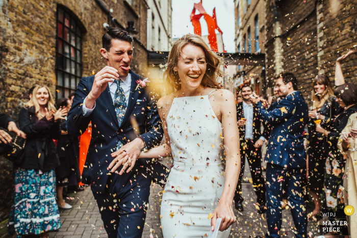 First Option Location Studios, Hackney, London wedding photography. Confetti is thrown at a bride and groom