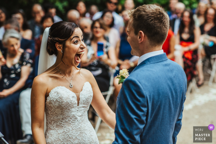 Wedding venue photography from the Château de Roquelune, Pezenas, France | A bride reacts with excitement at the end of her wedding ceremony