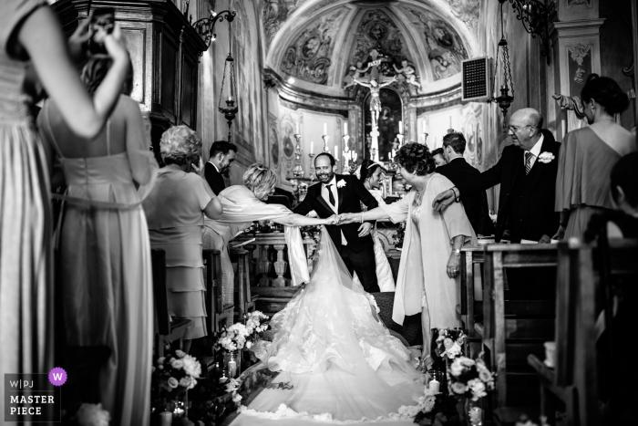 La Morra, Cuneo-ceremoniefotografie tijdens het kerkelijk huwelijk - bruidskleding die de begroeting van gasten blokkeert