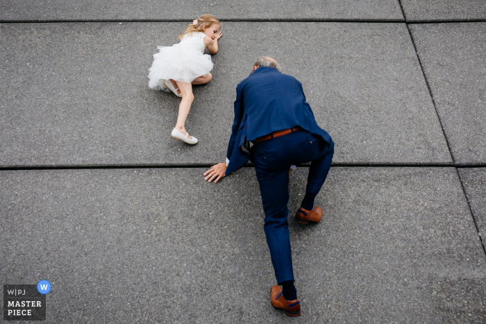 Outside the venue wedding photography, Hotel New York, Rotterdam, Netherlands - Daughter of the bride and groom and her granddad are climbing a wall.