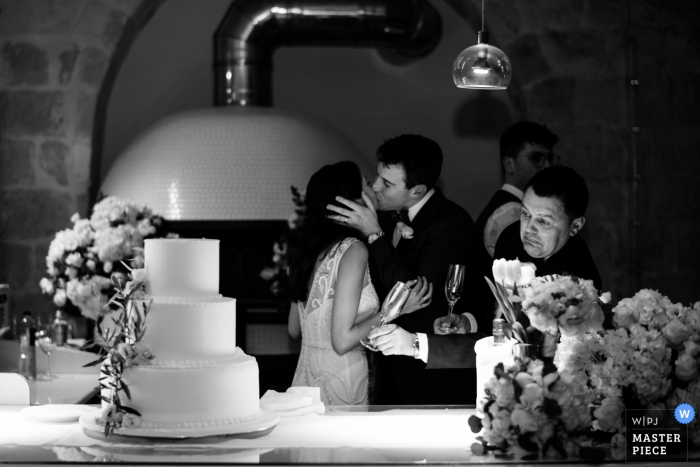 Apulia Wedding Reception Photography | Epic moment of the cake-cutting and kiss, the waiter decides it would be his time