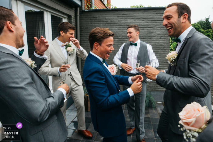 Antwerpen Flanders Wedding Reportage Photographer - bride and groom's house groomsmen are laughing with the sweatiness of one's groomsmen's shirt, early in the morning