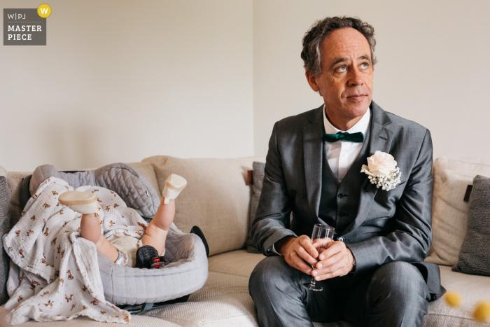 Antwerpener Hochzeitsfotograf Pro: Das Hausbaby von Braut und Bräutigam ist noch nicht zum Schlafen bereit, während ihr Opa neben ihr sitzt