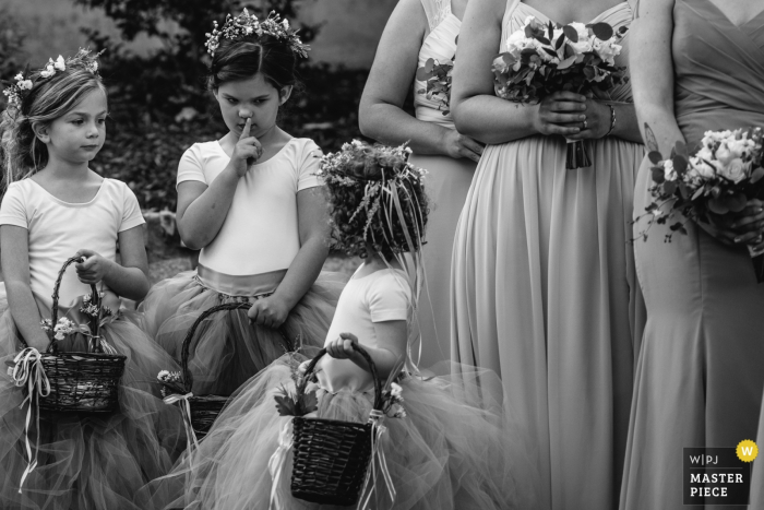 Outdoor wedding ceremony photos from venue Haue Valley: Pacific, Missouri - One flower girl shushes another during the ceremony.